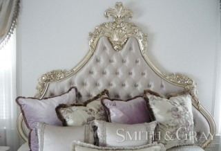 Handcarved and gilded bedhead with fabric and deep diamond buttoning and fabric buttons